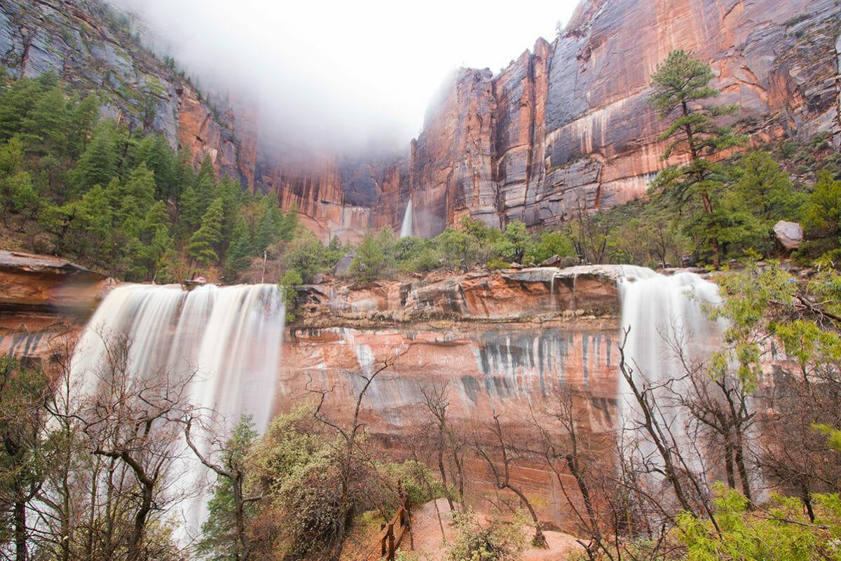 Waterfalls inside canyon after rain with foggy sky.