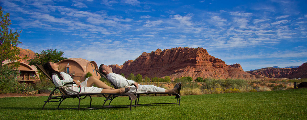 Couple lounging outside of spa with incredible scenic view of red rock formation in the distance.
