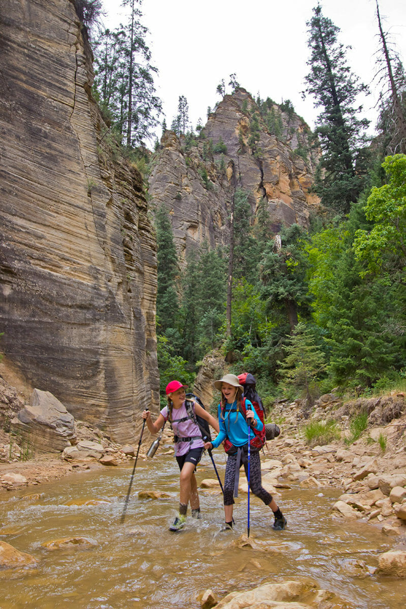 Girls hiking through water with canyon walls and pine trees behind.