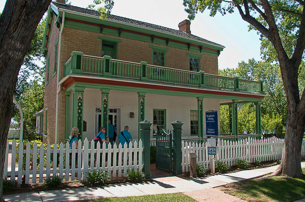 Exterior of historic home with brightly-colored paint and white picket fence.