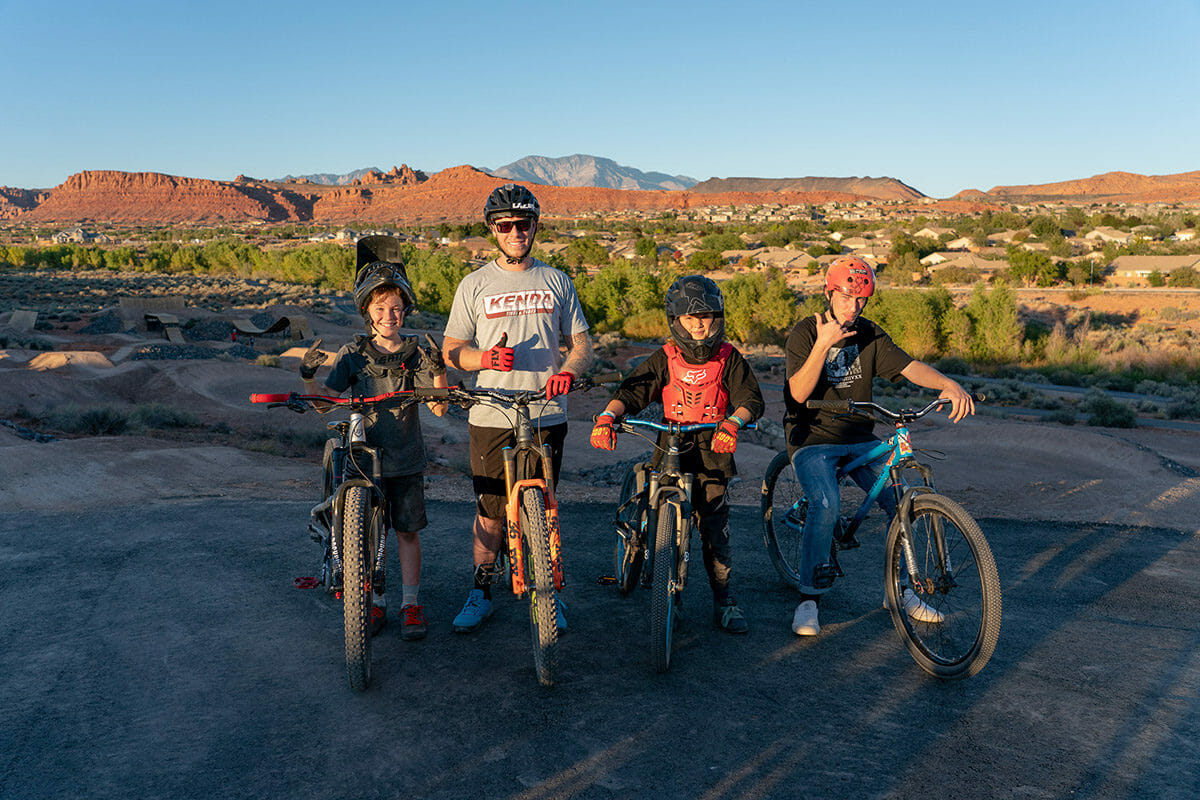 Smiling kids posing with mountain bikes.