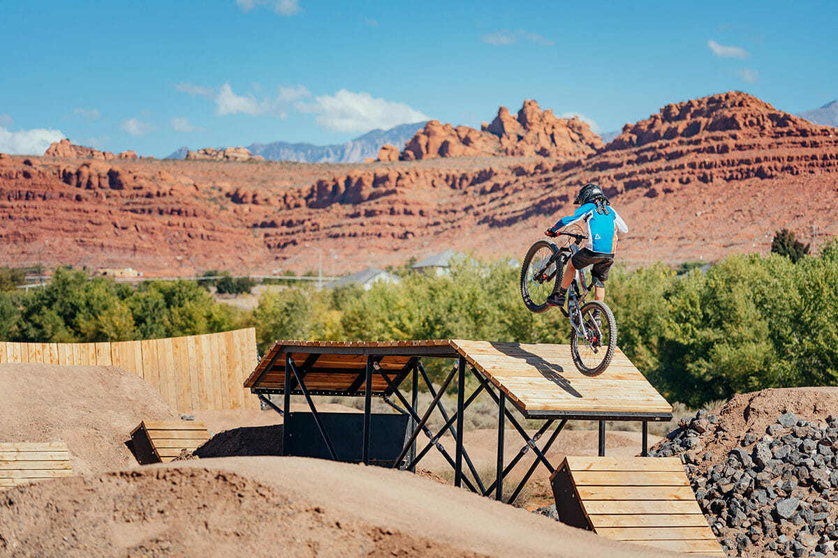 Boy on mountain bike jumping from wooden ramp.