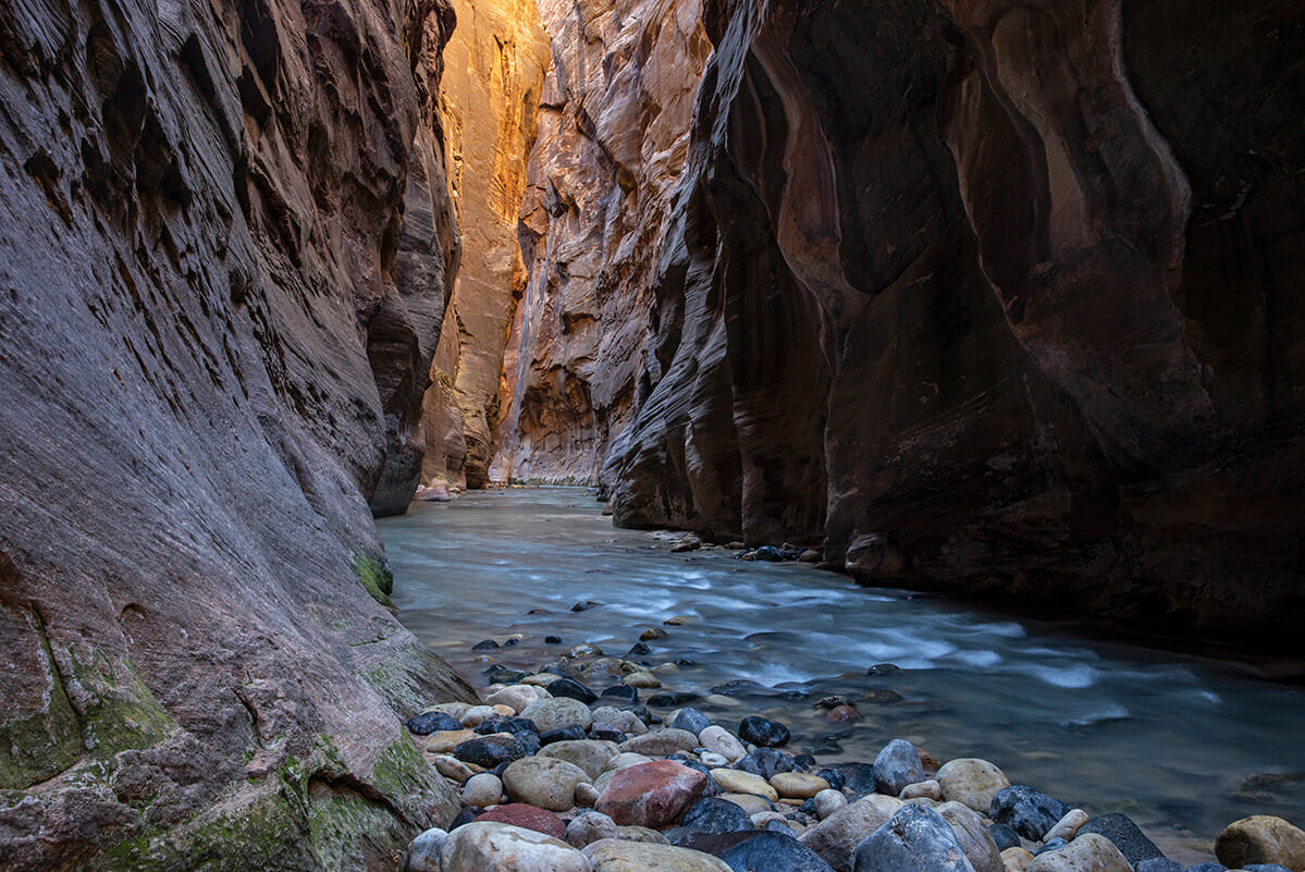 View down a slot canyon with river flowing over smooth rocks.