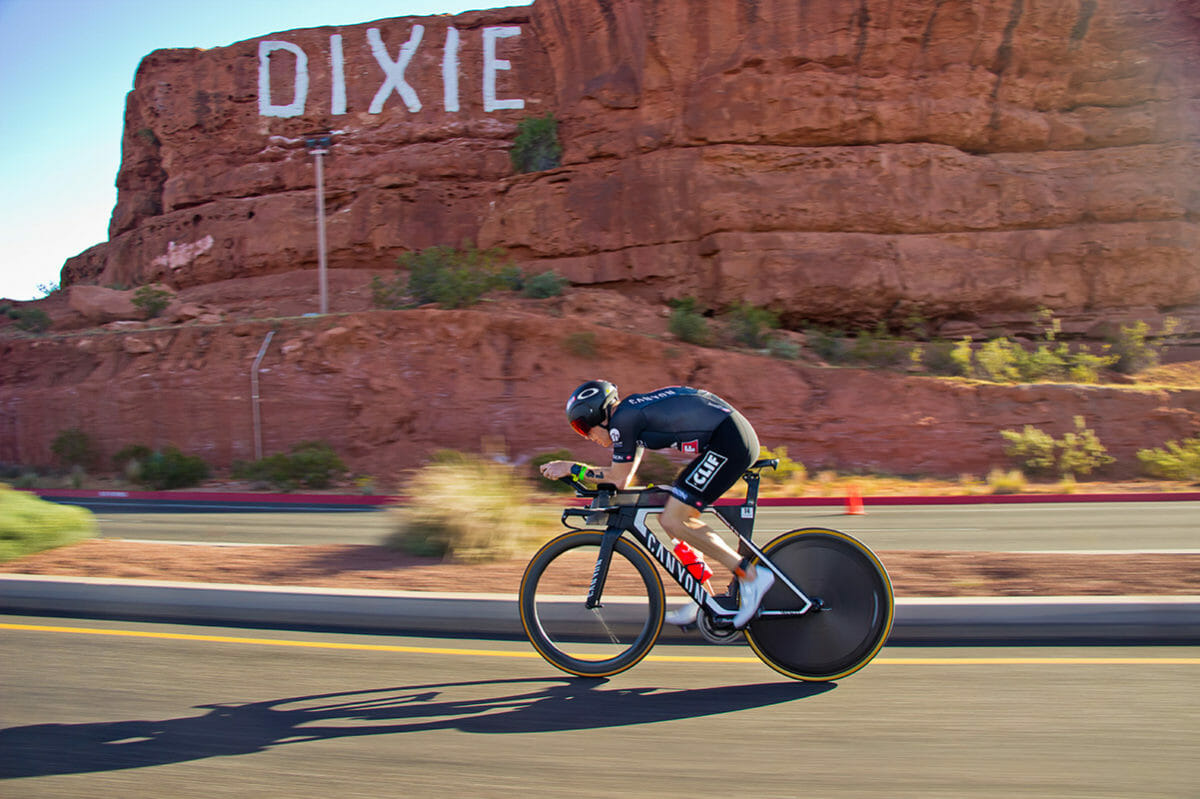 Triathlete cycling past red rock formation.