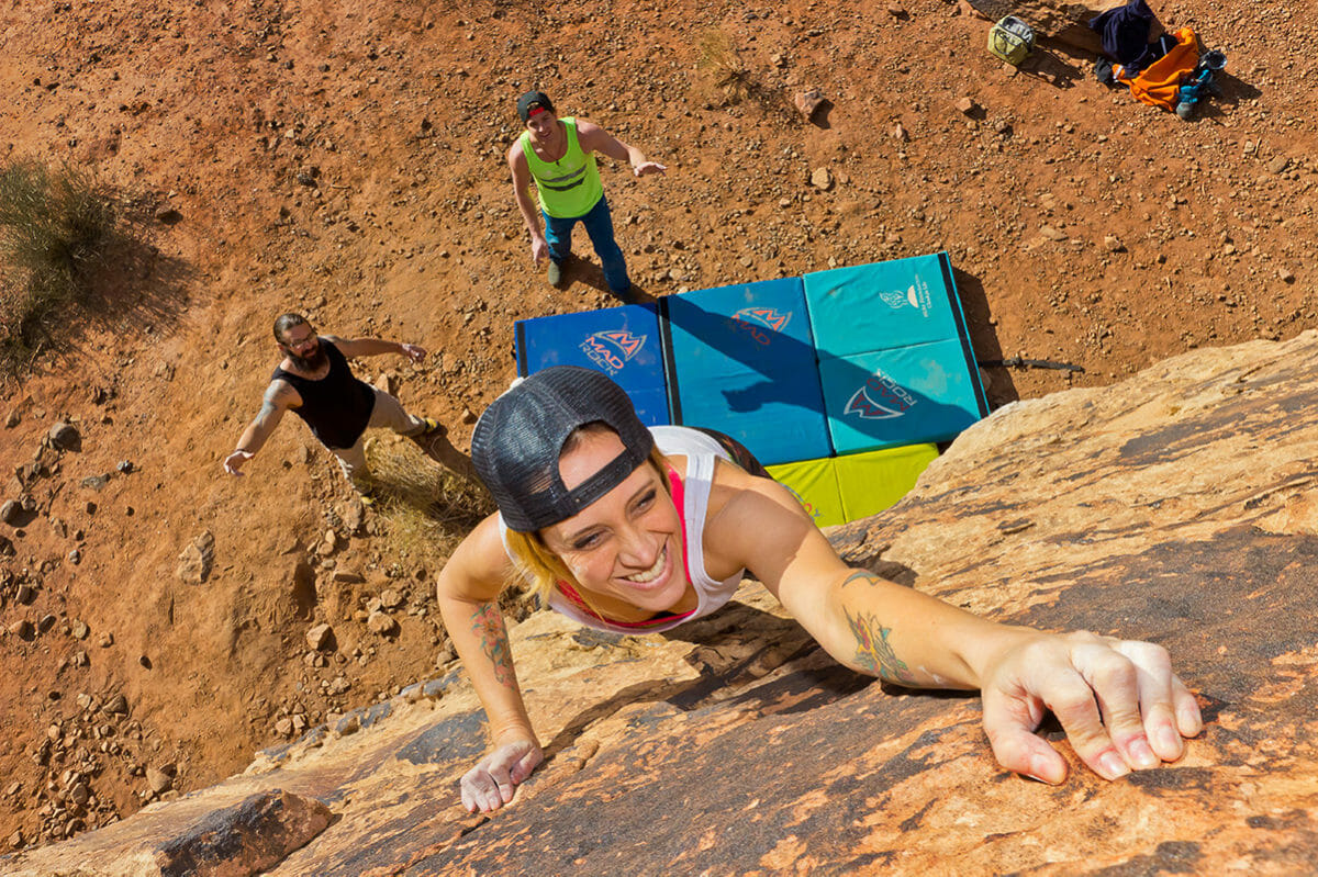 View of female climber reaching up for a hand hold while two men spot below.