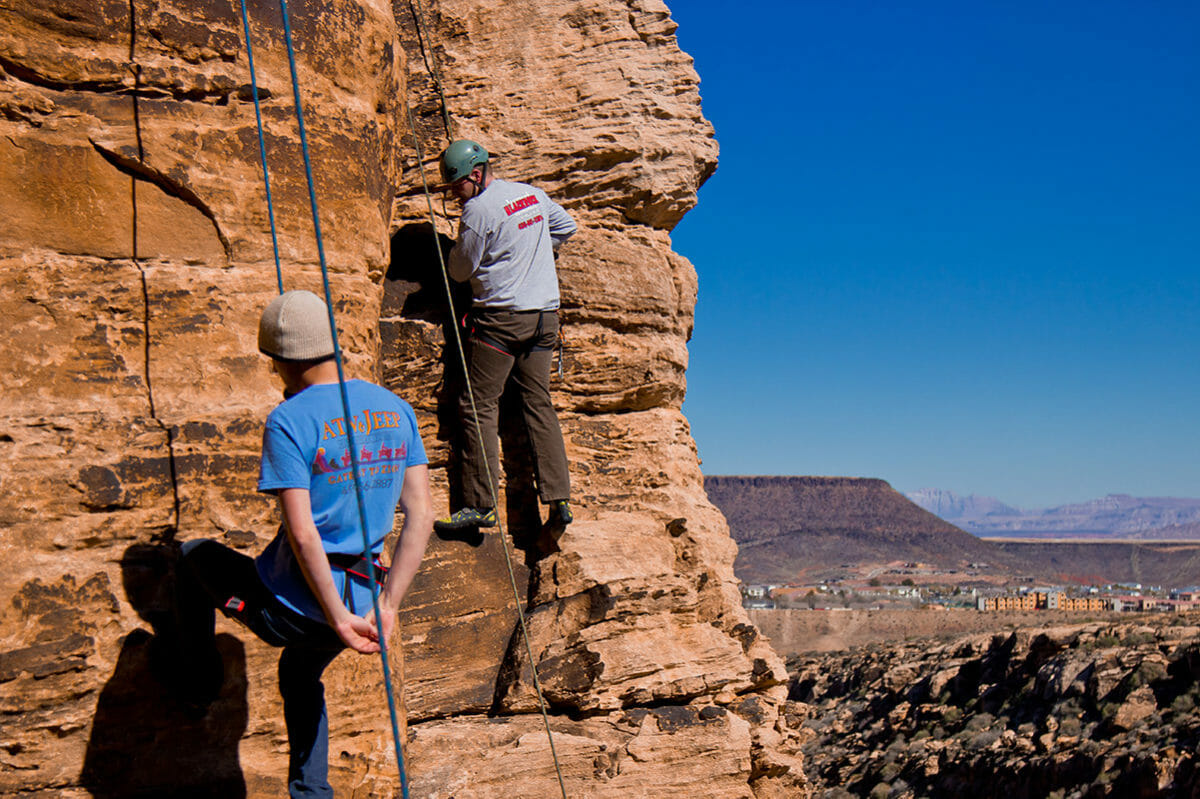 Two men rock climbing with supporting ropes.