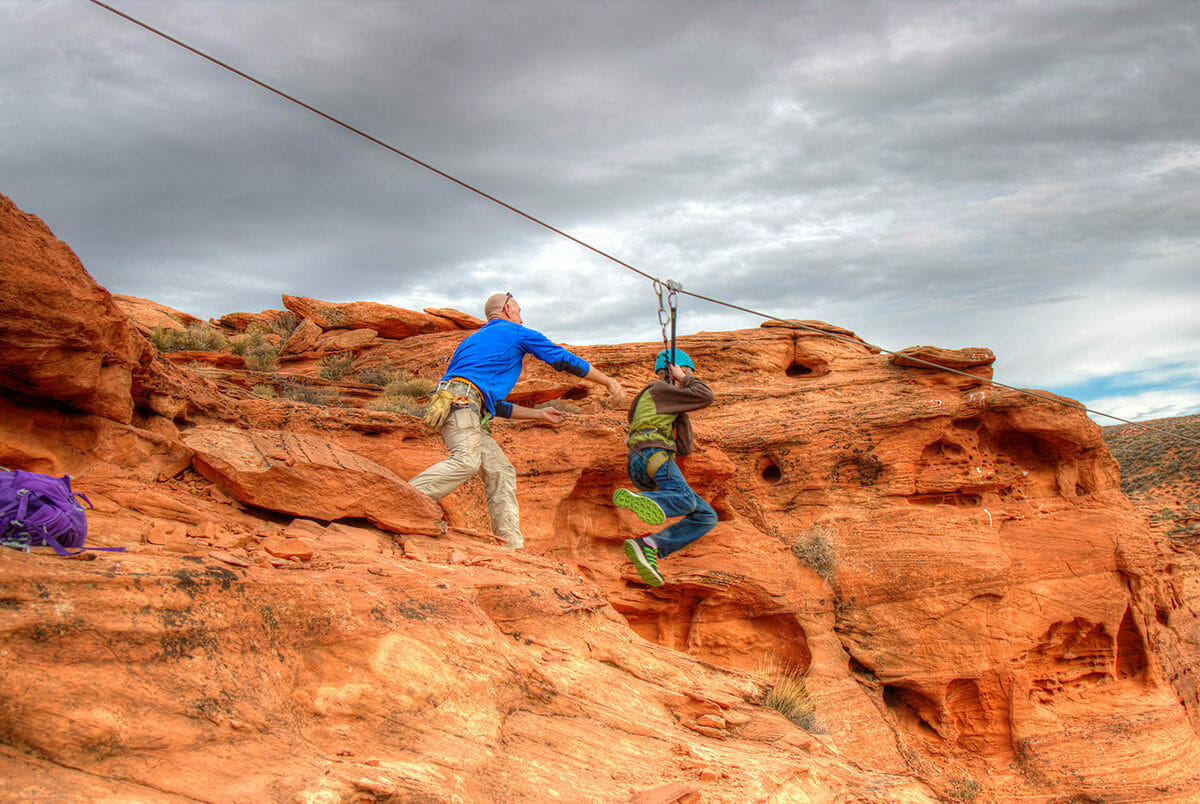 Man pushing young boy off cliff on zipline.