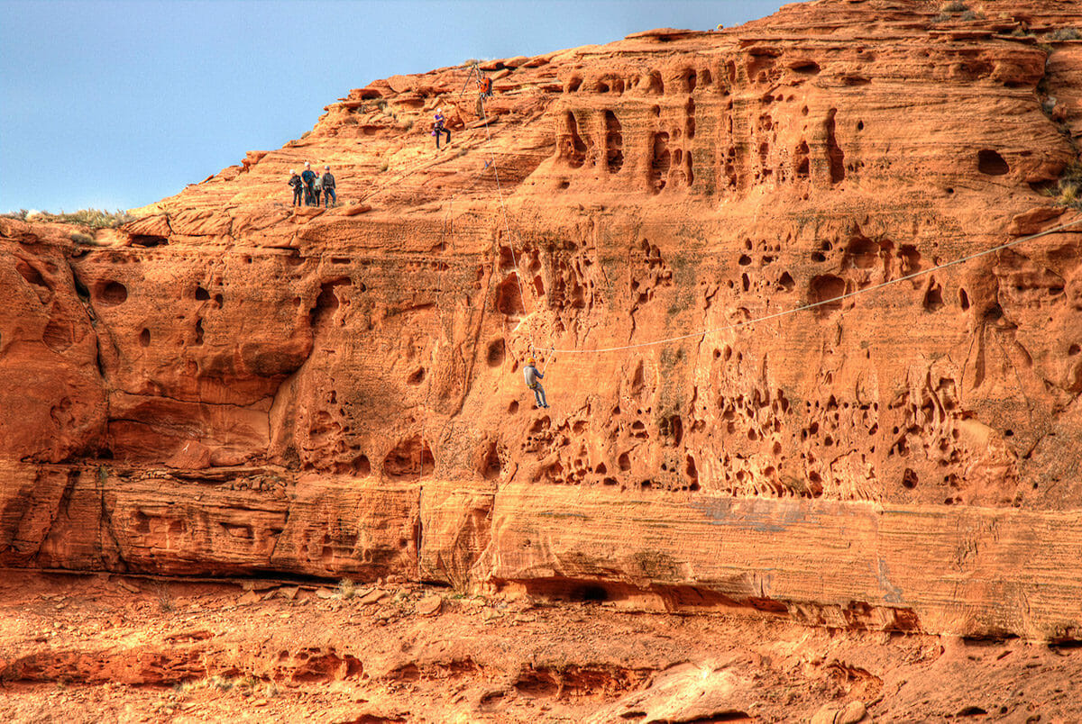 Wide view of man on zipline over canyon.