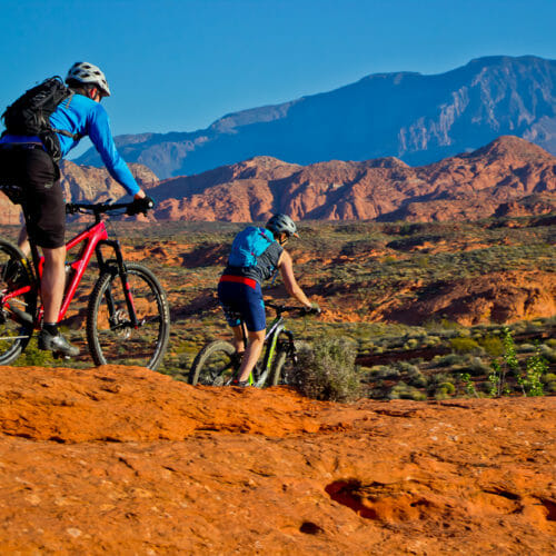 Couple on mountain bikes dropping down