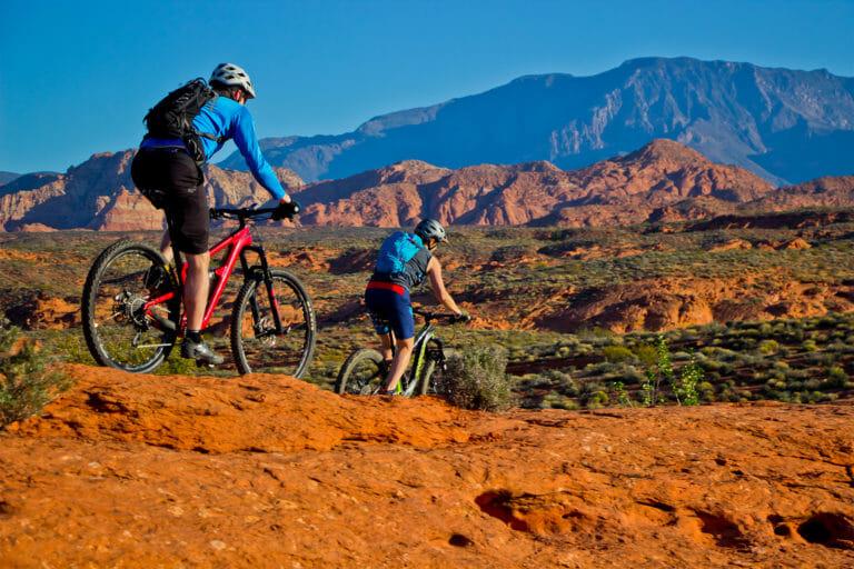 Couple on mountain bikes dropping down