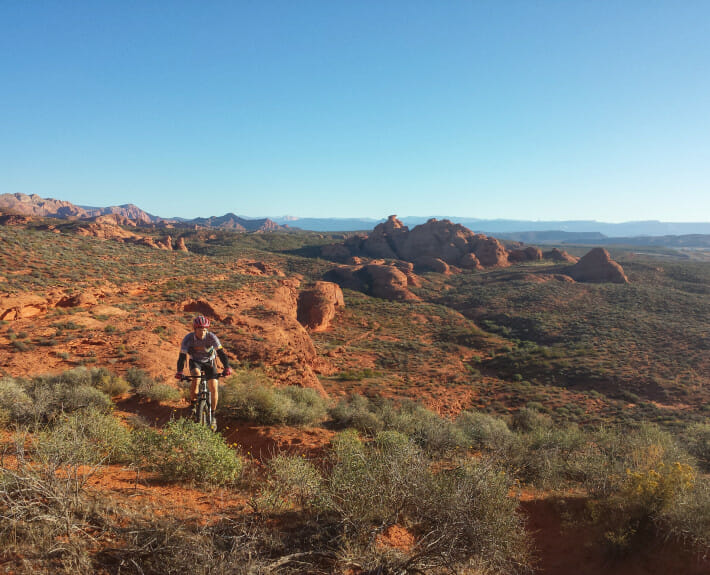 Mountain biker on desert trail with red rock formation in the background.