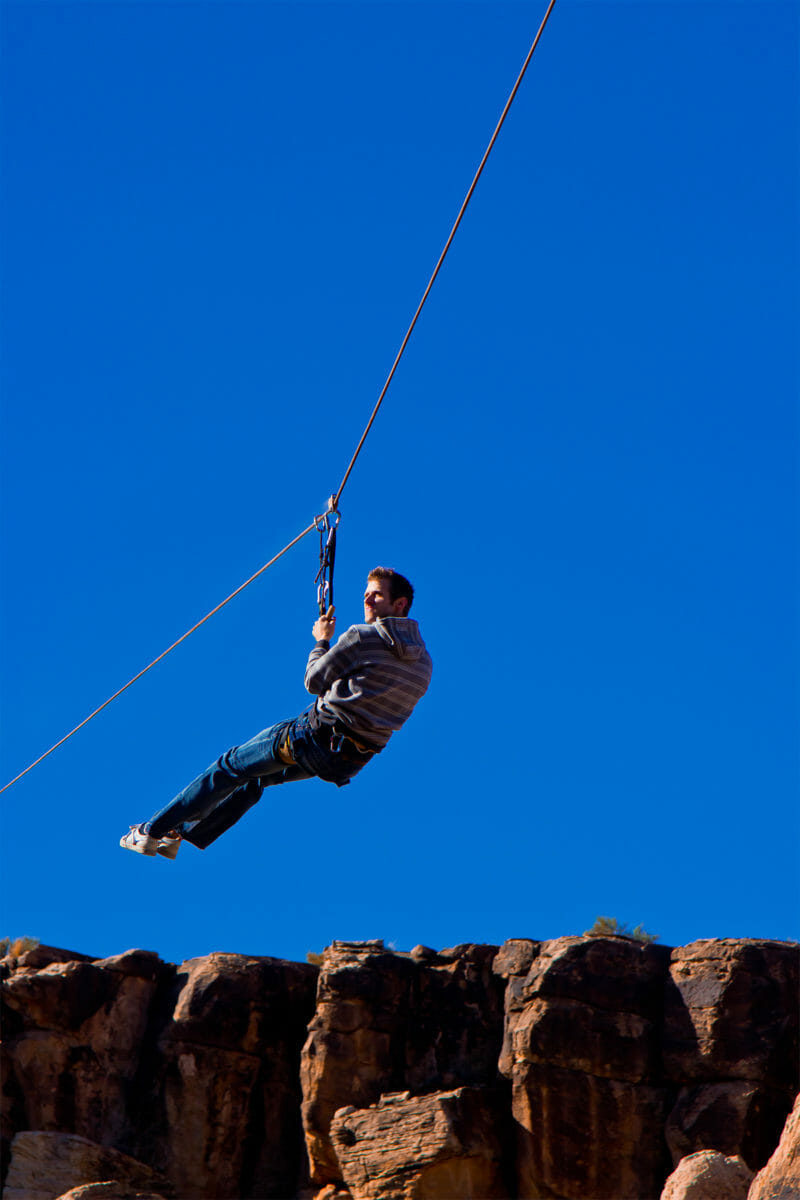 Ziplining man with a blue sky