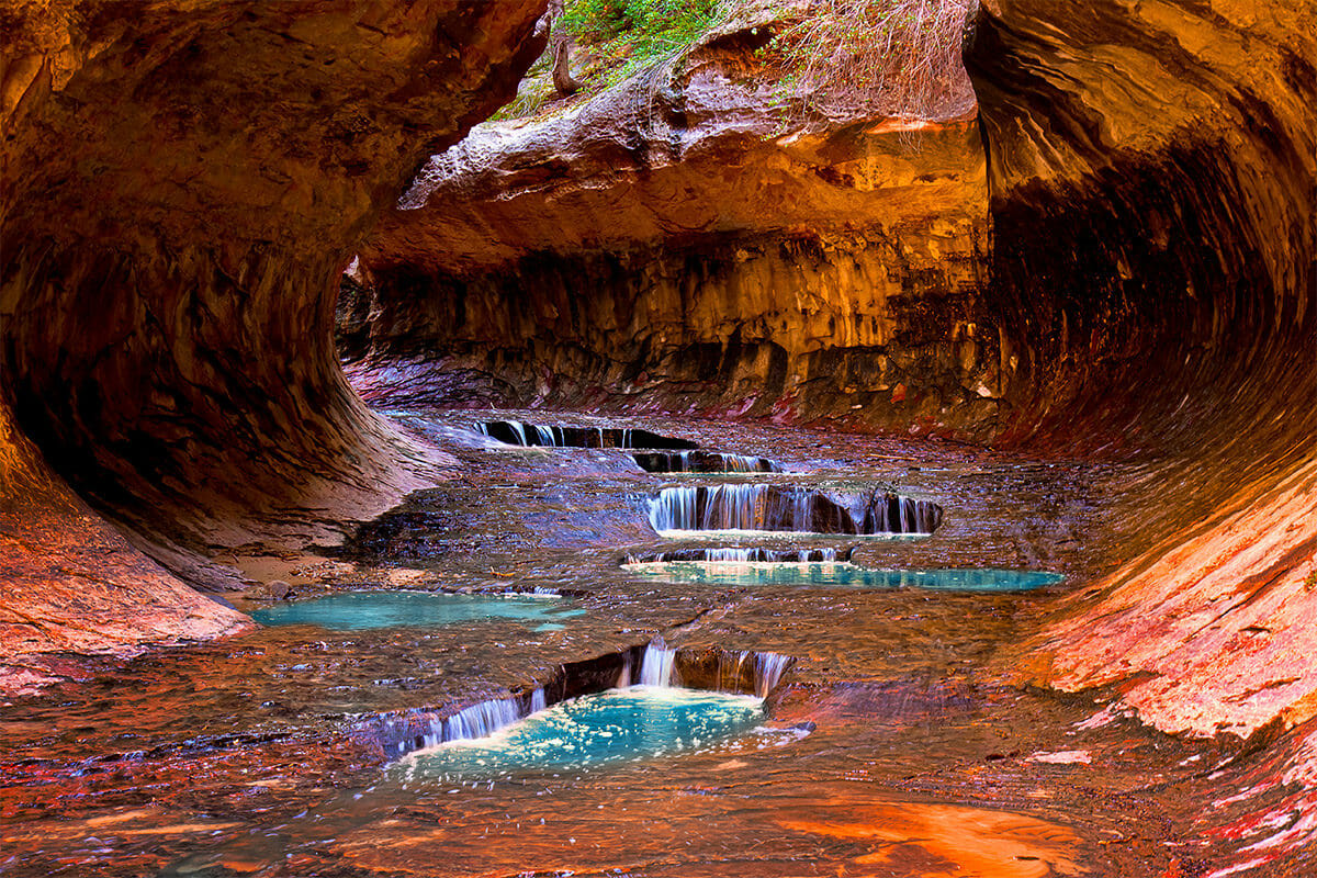 Turquoise pools of water in red, tunnel-shaped rock formation.