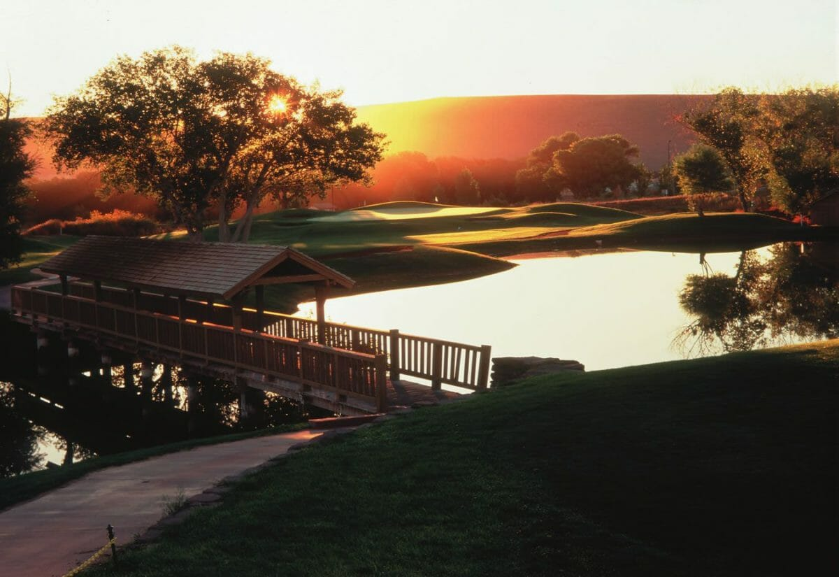 Sun rising over wooden bridge over pond at golf course.