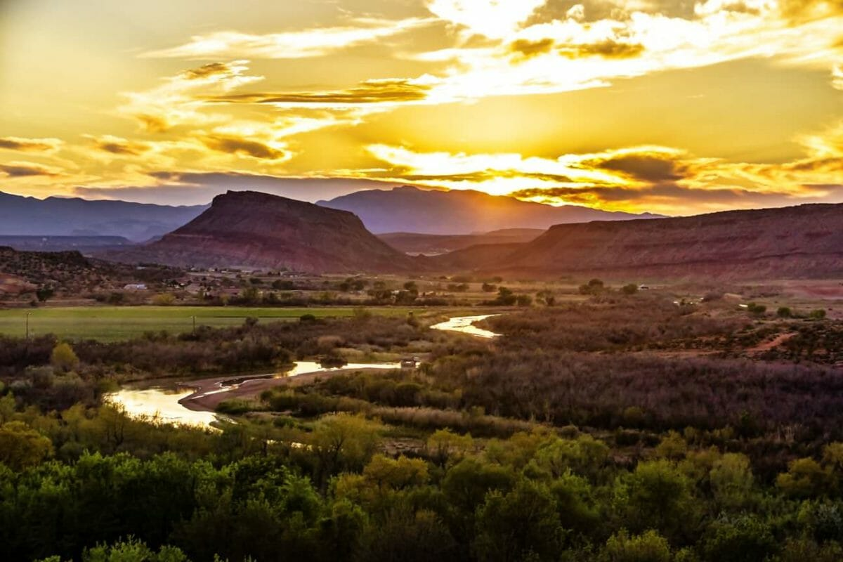 Sun rising over mountains and reflecting off of winding river.
