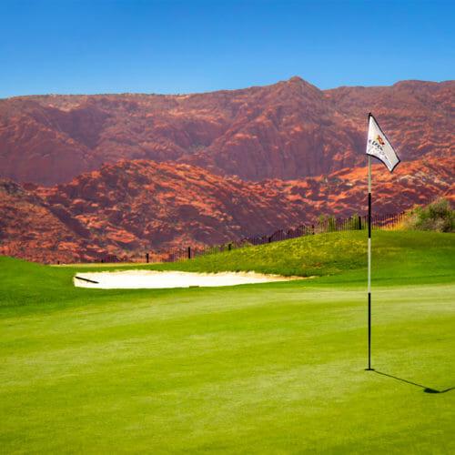 Zászló a golf zöld, egyenetlen vörös sziklák a háttérben, fényes kék ég alatt