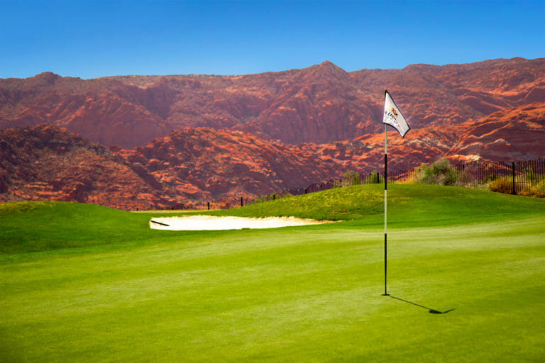 Flag on golf green with rugged red rocks in the background under a bright blue sky