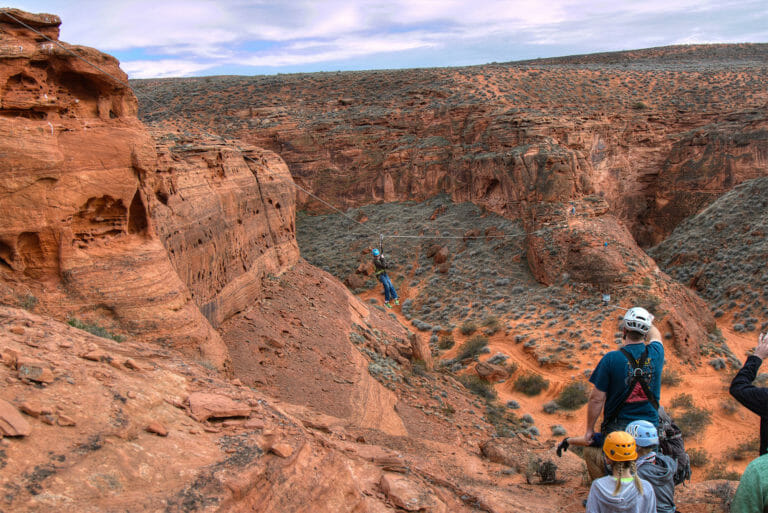 Person riding zip line over canyon