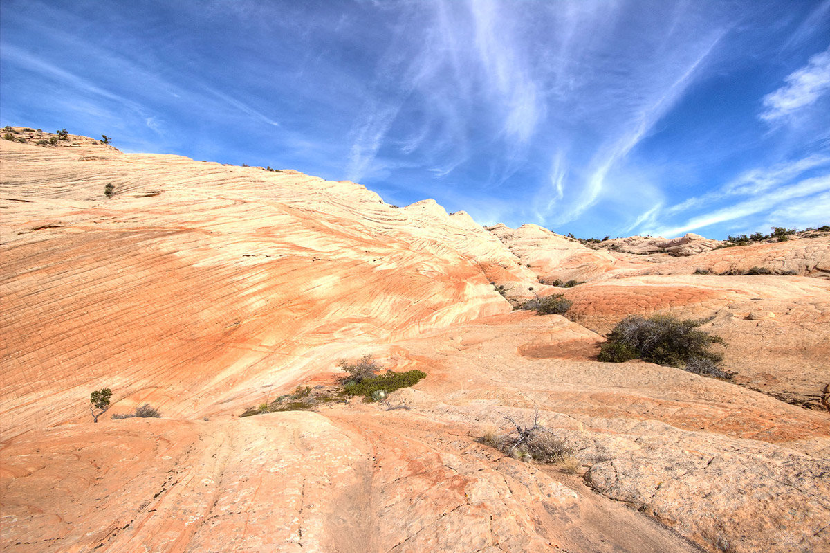 Red and white colored rock formation under bright blue sky