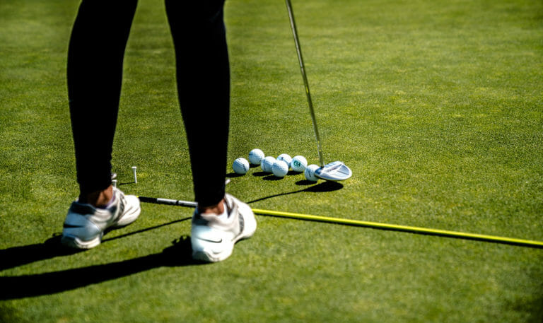Feet of female golfer with putter and six balls