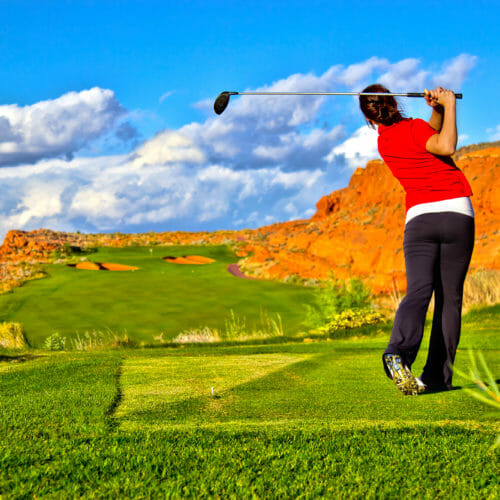 Left-handed female golfer in mid-swing