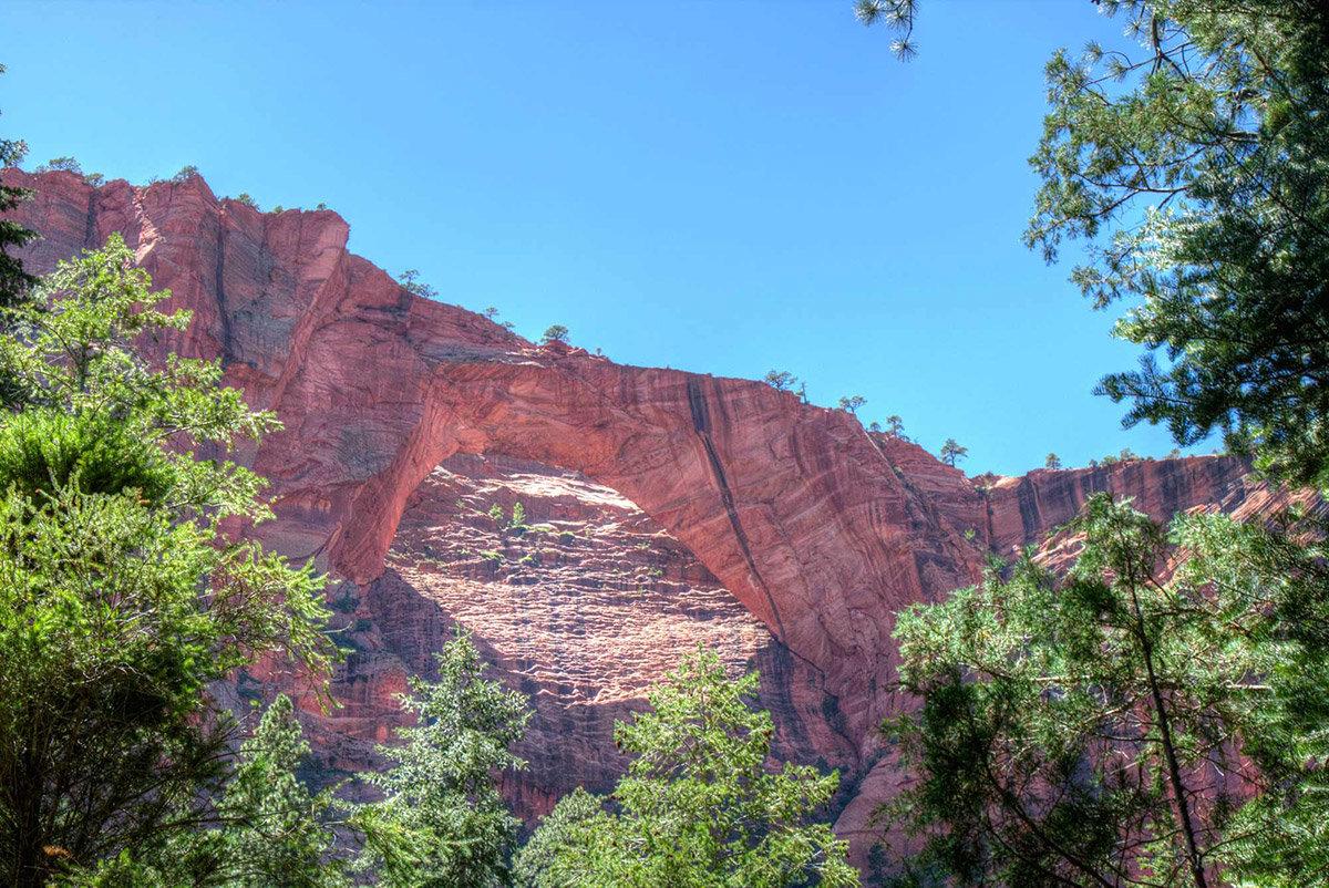 Obrovský červený skalní oblouk s modrou oblohou nad