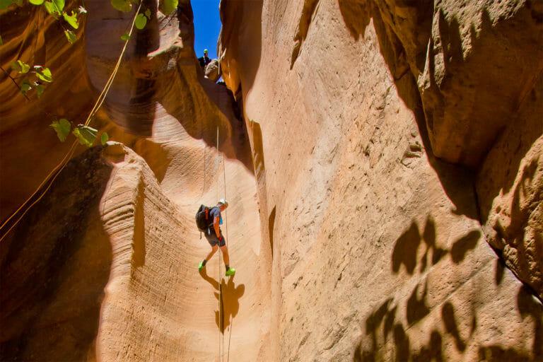 Man rappelling down slot canyon