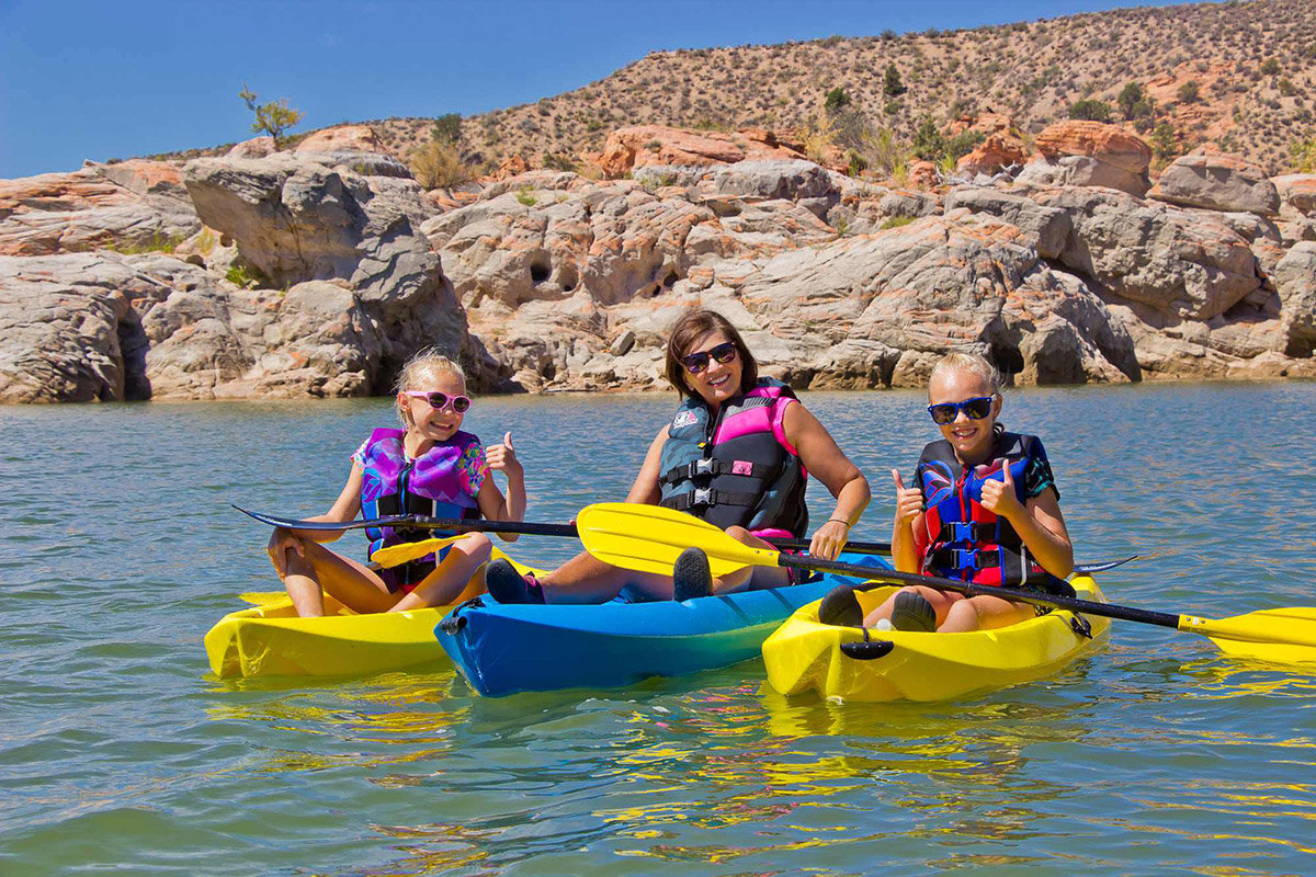 Smiling mother and young daughters kayaking