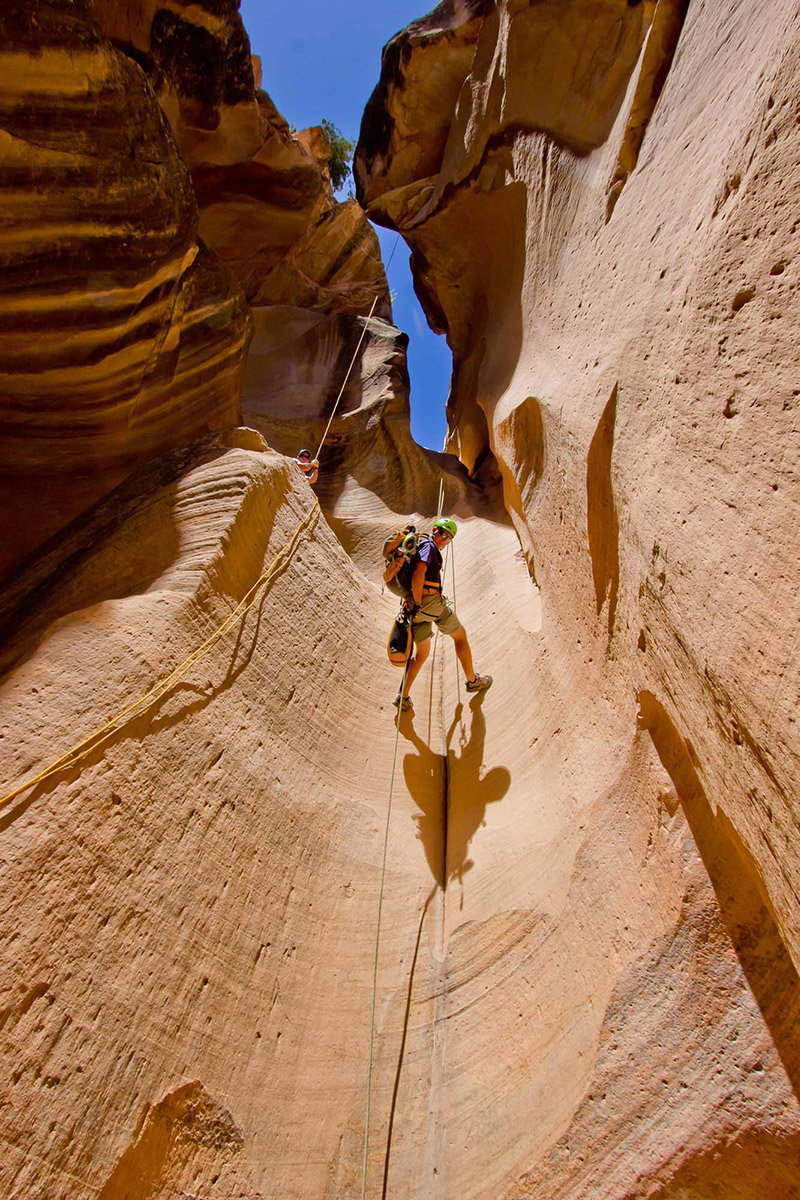 Man rappelling down smooth cliff