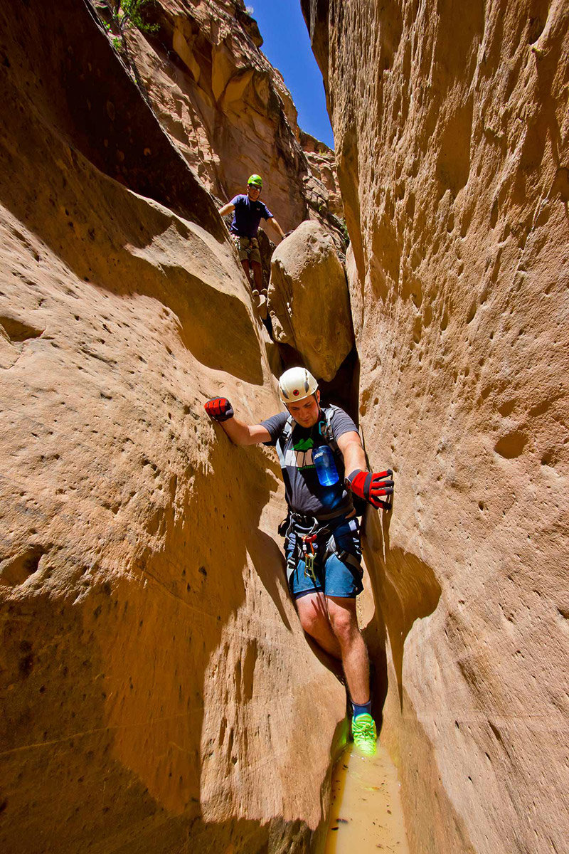Man hiking through tight slot canyon