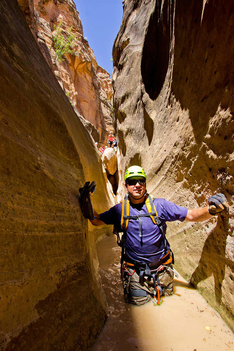 Man in waist-deep water in slot canyon