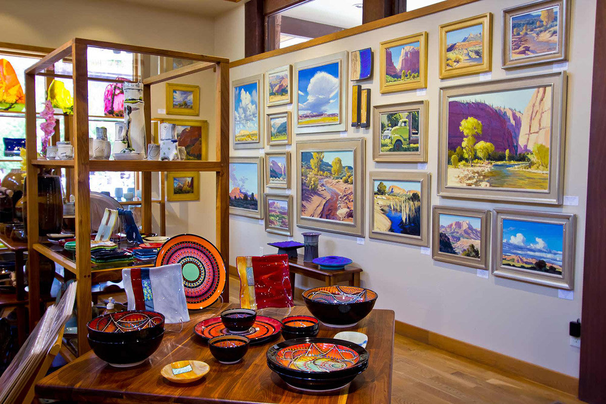 Collage of brightly-colored paintings on gallery wall with decorative bowls in foreground