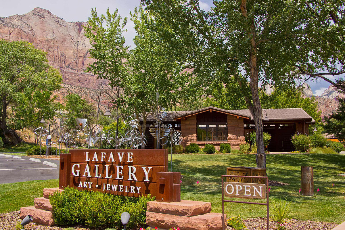 Sign reading LaFave Gallery in front of building with trees and large mountain behind
