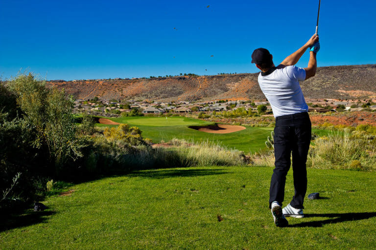 View from behind of a male golfer in mid swing.
