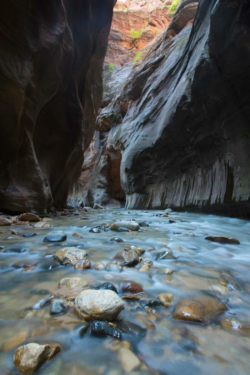 Stone-covered canyon floor with water.