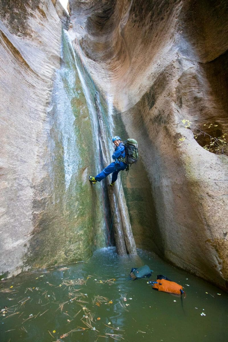 Woman rappelling down a waterfall