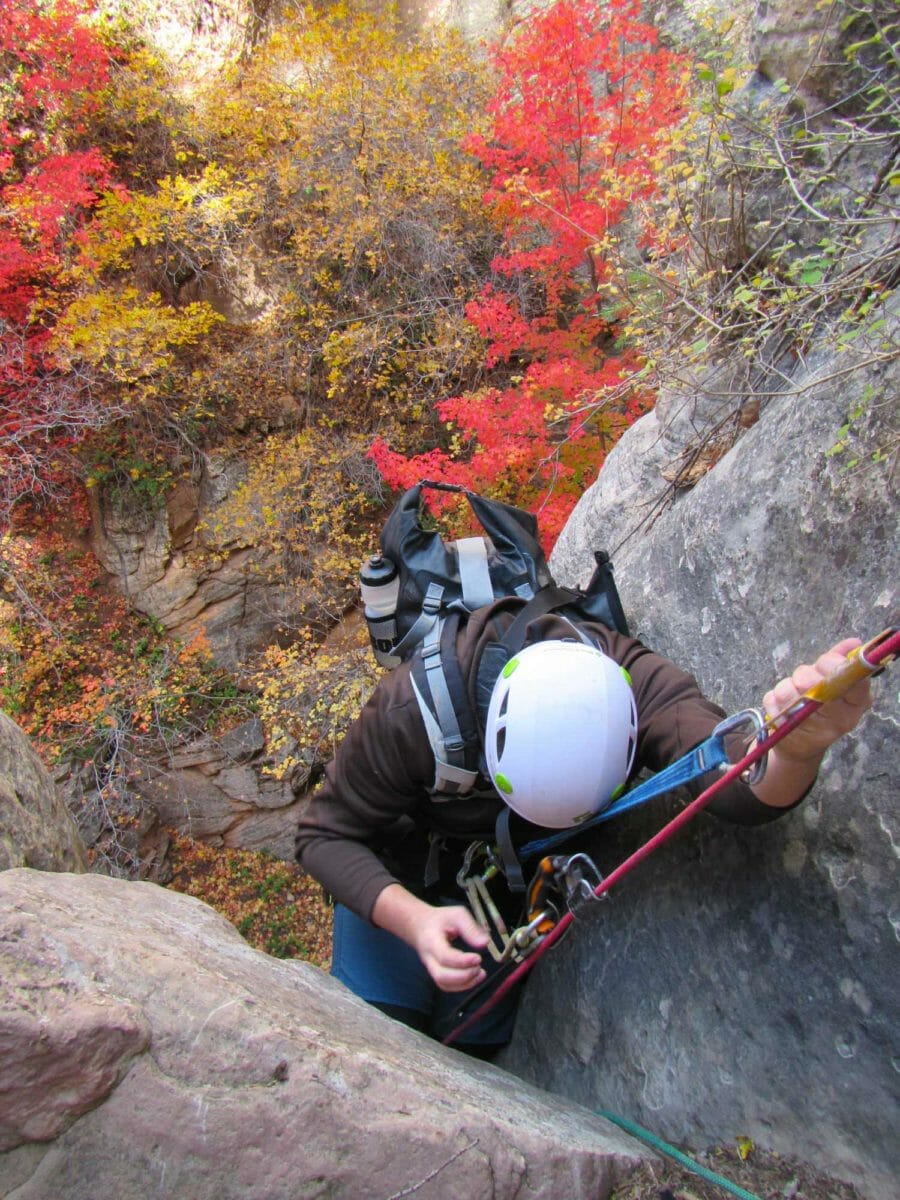 Man climbing up a canyon with climbing gear.