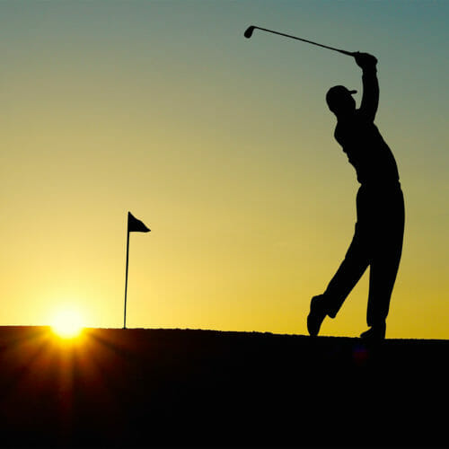 Silhouette of golfer in mid swing at sunset.