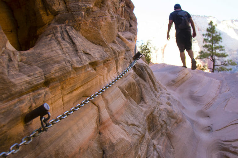 Man hiking up Hidden Canyon with chain
