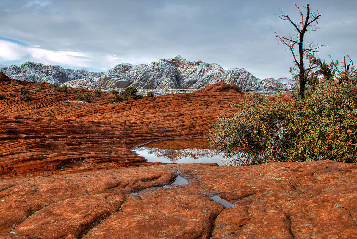 Snow covered mountain peaks behind red rock formations.
