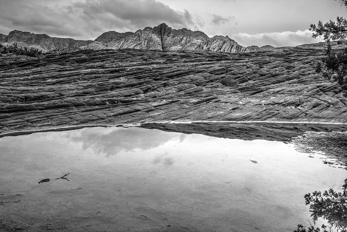 Black and white photo of pooled water on rock formations.