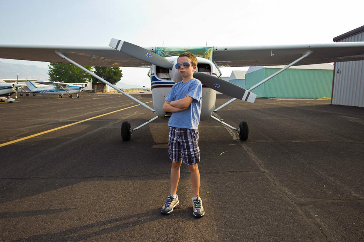 Boy posing in front of aerial tour plane.