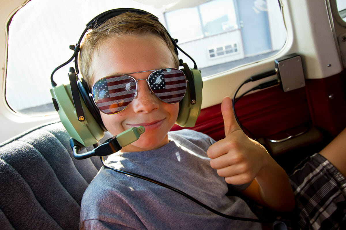 Boy in airplane with headset giving thumbs up.