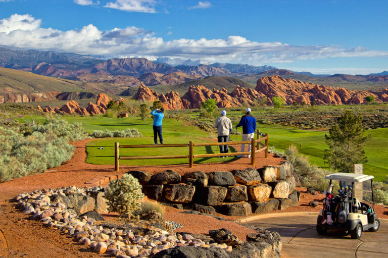Group of three men teeing off on desert golf course with red rock formation in distance and white clouds in a bright blue sky.