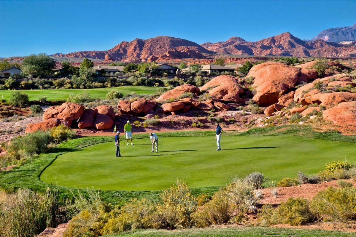 Foursome of golfers on a desert green.