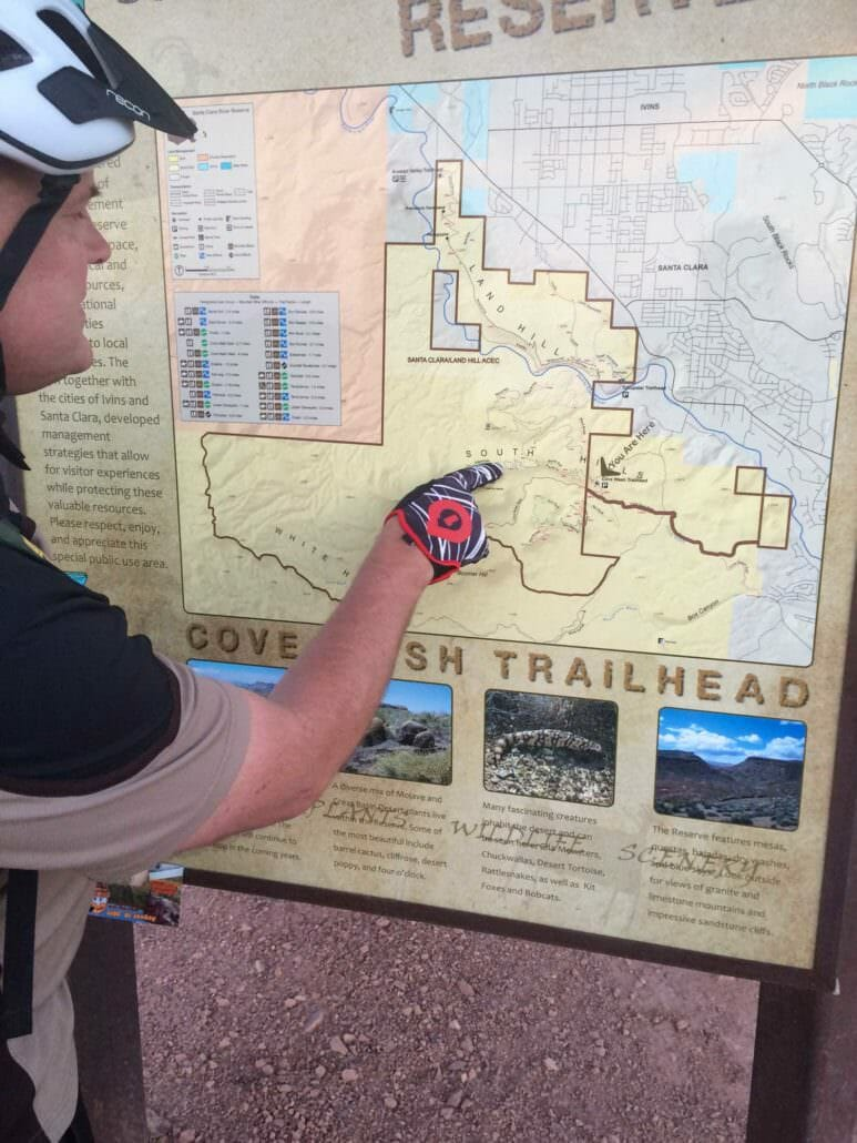 Mountain biker reading trailhead sign.