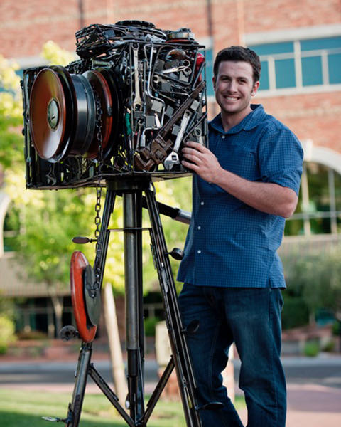 Photographer standing next to sculpture of a camera.