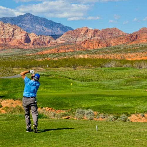 Man in blue shirt mid swing with scenic view of golf course surrounded by red mountains.