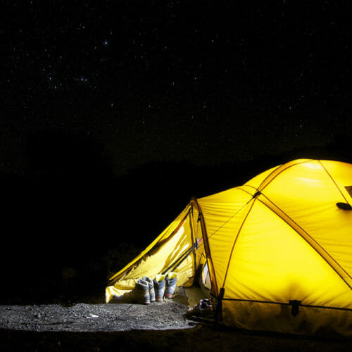 Glowing yellow tent with dark skies