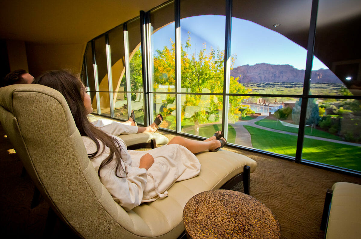 Couple lounging at spa in front of large window with scenic view of mountains.